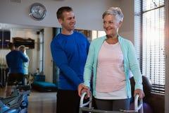 Physiothérapeute aidant le patient supérieur pour marcher avec le cadre de marche Photo libre de droits