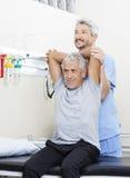 Physiothérapeute Assisting Senior Man dans l'exercice au cent de réadaptation Image libre de droits