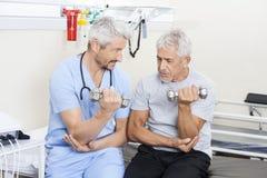 Physiothérapeute Assisting Senior Man dans les haltères de levage image libre de droits