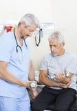Physiothérapeute Assisting Senior Patient dans les haltères de levage Image stock