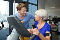 Physiothérapeute avec la femme supérieure à l'aide de la machine d'exercice Photographie stock libre de droits