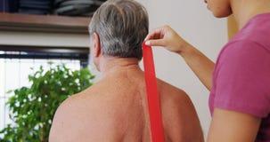 Physiothérapeute collant la bande sur le dos supérieur 4k de patient banque de vidéos