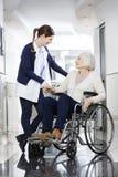 Physiothérapeute Consoling Senior Patient dans le fauteuil roulant images stock