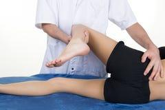 Physiothérapeute de mâle adulte traitant la jambe d'un patient féminin Image stock