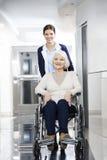 Physiothérapeute de sourire Pushing Senior Woman dans le fauteuil roulant Images libres de droits