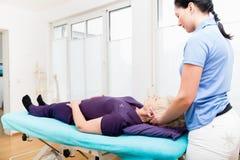 Physiothérapeute de visite de femme supérieure pour le massage images libres de droits