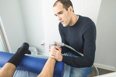 Physiothérapeute donnant la thérapie de pied à un patient dans la clinique Concept avancé de physiothérapie image stock