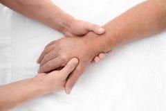 Physiothérapeute donnant le massage de main au patient supérieur, photo libre de droits