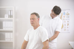 Physiothérapeute examinant l'homme d'homme aîné Photo stock