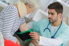 Physiothérapeute examinant le bras de la femme supérieure dans la clinique Images stock