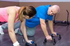Physiothérapeute féminin d'entraîneur de forme physique aidant le client supérieur faisant des pompes Image stock