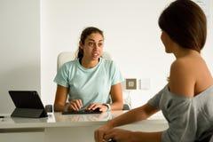 Physiothérapeute féminin expliquant le diagnostic à sa patiente de femme Photographie stock