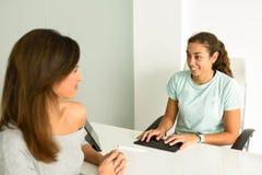 Physiothérapeute féminin expliquant le diagnostic à sa patiente de femme Photo libre de droits