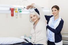 Physiothérapeute féminin Helping Senior Patient avec l'exercice de main Photo libre de droits