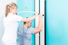 Physiothérapeute faisant la réadaptation de sport avec le patient Images libres de droits