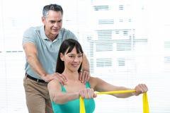 Physiothérapeute guidant la femme enceinte avec l'exercice Photo stock