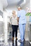 Physiothérapeute Helping Senior Patient avec des béquilles Image libre de droits