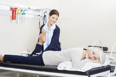 Physiothérapeute Helping Senior Woman avec l'exercice de jambe Photos stock