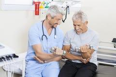 Physiothérapeute heureux Assisting Senior Man dans les haltères de levage Image libre de droits