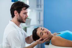Physiothérapeute masculin donnant le massage principal au patient féminin Images stock