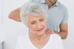 Physiothérapeute masculin massant le cou d'une femme supérieure Photo stock