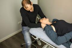 Physiothérapeute massant le visage d'une jeune femme Physiothérapie et relaxation de concept photographie stock libre de droits
