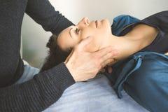 Physiothérapeute massant le visage d'une jeune femme Physiothérapie et relaxation de concept image libre de droits