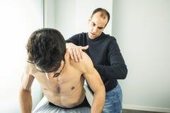 Physiothérapeute massant une épaule de jeune homme physiothérapie photos stock