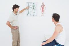 Physiothérapeute montrant à patient quelque chose sur le diagramme squelettique Photos stock