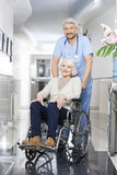 Physiothérapeute Pushing Senior Woman dans le fauteuil roulant Photos stock