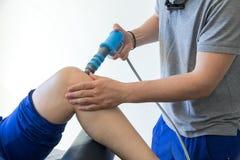 Physiothérapie du genou et le pied avec l'onde choc Photo stock