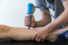 Physiothérapie du genou et le pied avec l'onde choc Images libres de droits