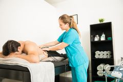Physiotherapeut Applying Electro Stimulation unterstützen an vom Kunden lizenzfreies stockfoto