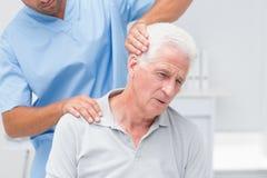 Physiotherapeut, der dem älteren Patienten Physiotherapie gibt Stockfotos