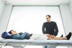 Physiotherapeut, der ein Knie der jungen Frau behandelt Konzept von Physiotherapie und von Rehabilitation stockfoto