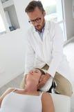 Physiotherapeut, der einem Frauenpatienten Massage macht Stockbilder