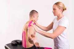 Physiotherapeut, der kinesio Band setzt Stockfotos