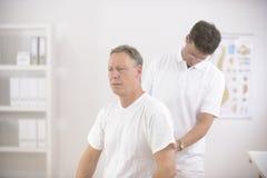 Physiotherapeut, der Mann des älteren Mannes überprüft Stockfoto