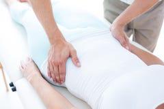 Physiotherapeut, der seinen Patientenmagen überprüft Lizenzfreies Stockfoto