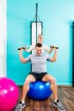 Physiotherapeut, der Sportrehabilitation mit Patienten tut Stockfotos