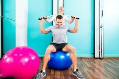Physiotherapeut, der Sportrehabilitation mit Patienten tut Stockbilder