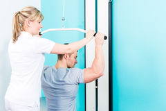 Physiotherapeut, der Sportrehabilitation mit Patienten tut Lizenzfreie Stockbilder
