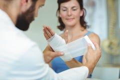 Physiotherapeut, der Verband auf verletzte Hand des Patienten setzt Stockbilder