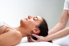 Physiotherapeut, der zurück vom Kopf der Frau bedrängt