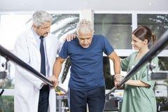 Physiotherapeuten, die älteren Patienten motivieren, um zwischen Paral zu gehen lizenzfreie stockfotografie