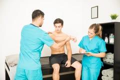 Physiotherapeuten-Examining Shirtless Customer-` s Hand während Cowork lizenzfreie stockbilder