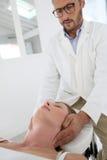 Physiotherapeutenfestlegungslage des Kopfes der Frau Stockbild
