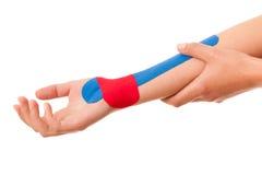 Physiotherapie - Arm stabilisiert mit kinesotape nach Verletzung Lizenzfreie Stockfotografie