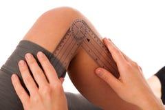 Physiotherapie - Therapeut, der mit dem Patienten verwendet gonomete excercising ist Lizenzfreies Stockfoto