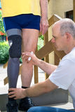 Physiotherapist adjusting prosthetic leg. Physiotherapist adjusting gray and black prosthetic leg for unidentifiable male patient in blue shorts and yellow shirt Stock Photos